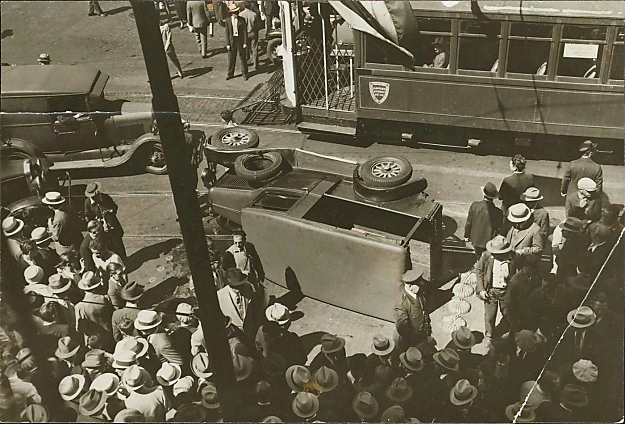 Men with hats gather at the site of an overturned car during the 1934 General Strike in San Francisco